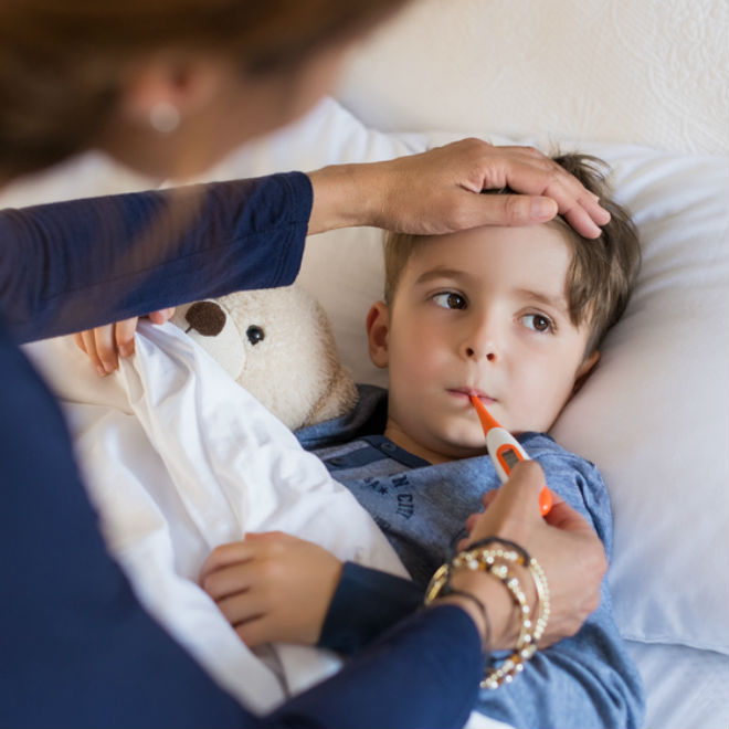 sick child with thermometer in his mouth home from school