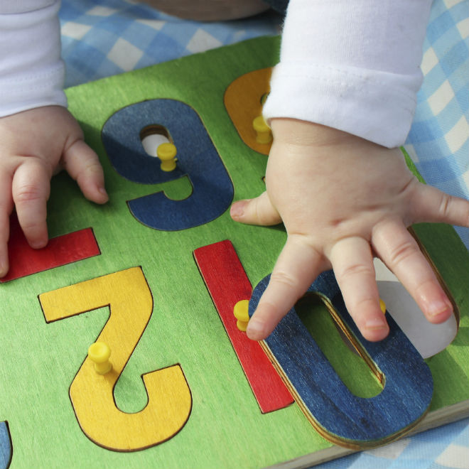 A toddler's hands matches numbers