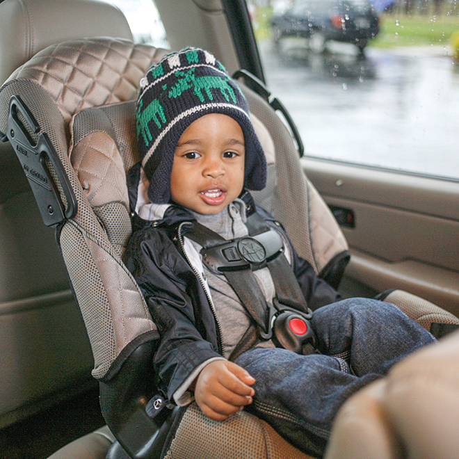 Toddler strapped into car seat