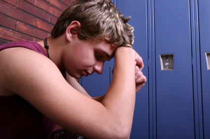 teenage boy with head down in front of locker