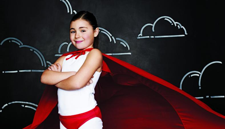 a little girl posing confidently in a superhero outfit