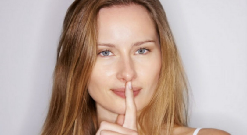 woman with finger over lip making the be quiet symbol