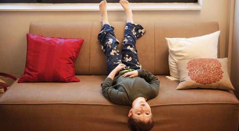 Young boy laying on a couch