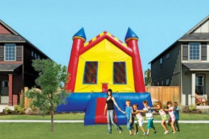 Daycare teacher walking with kids outdoors beside a jumping castle