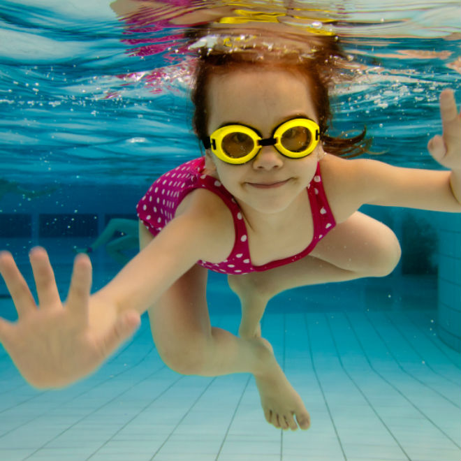 a little girl swimming with goggles on
