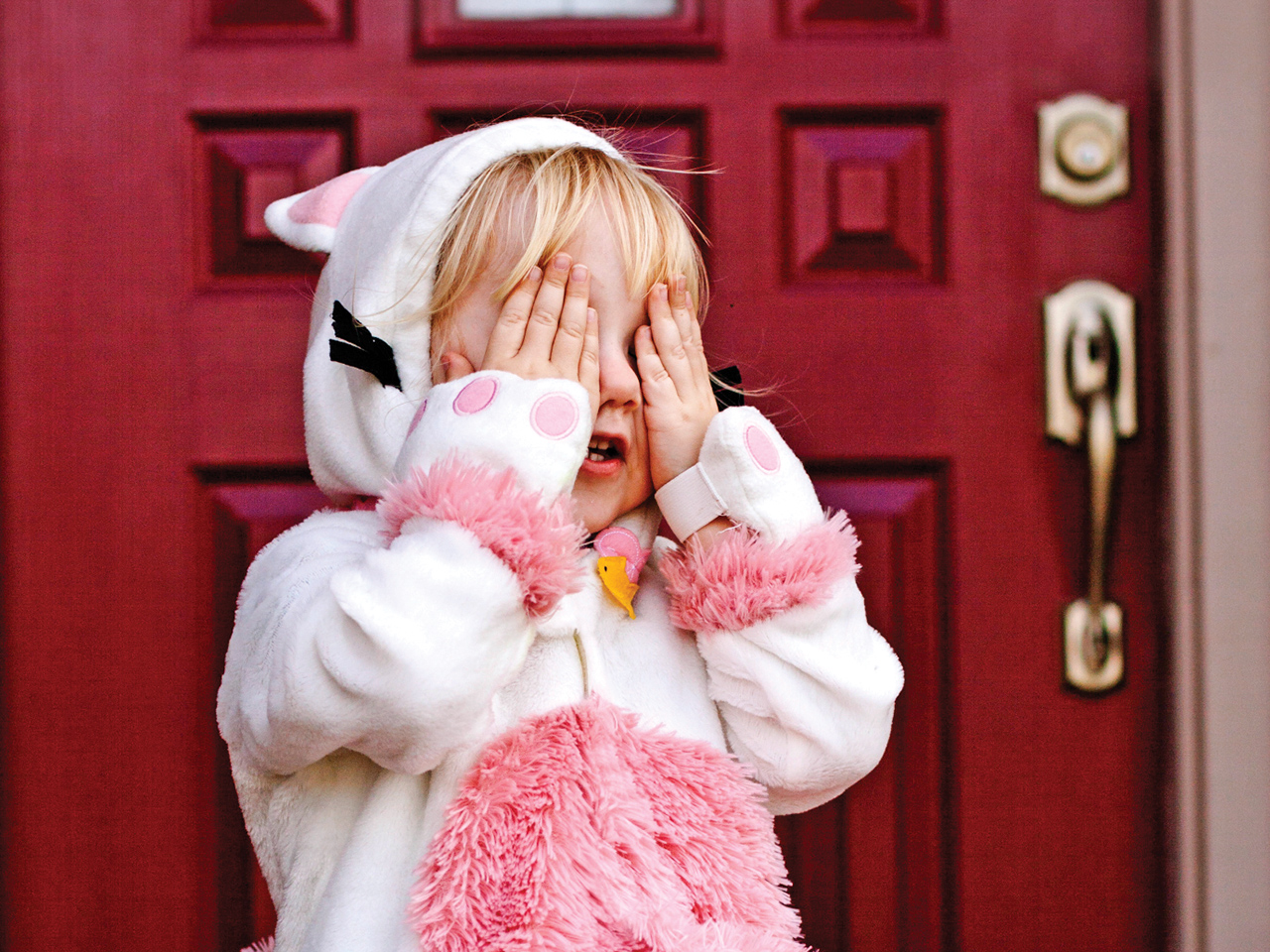 A kid in a cat costume covering her eyes