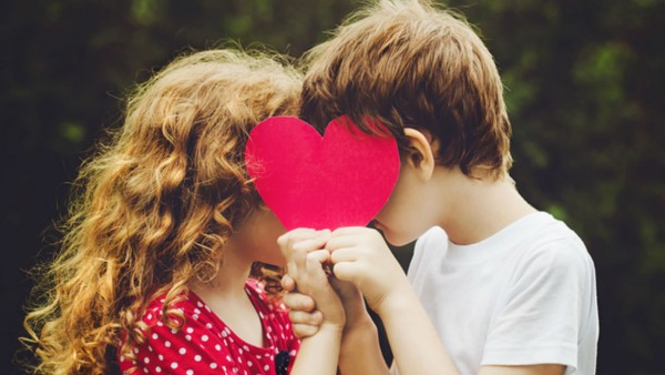 Two kids holding a heart that covers their face