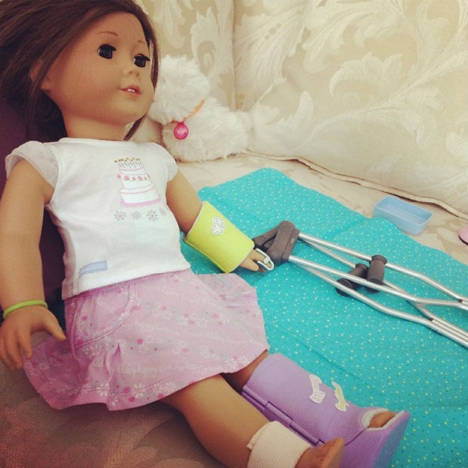 Picture of a doll with a toy pair of crutches
