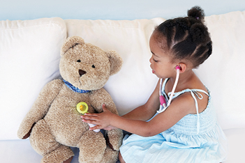 A little girl playing doctor on a stuffed animal