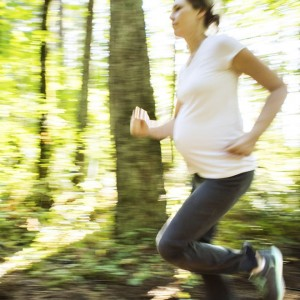 Pregnant woman going for a run through the woods