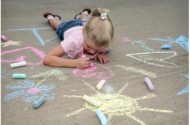 little girl drawing with chalkboard on pavement
