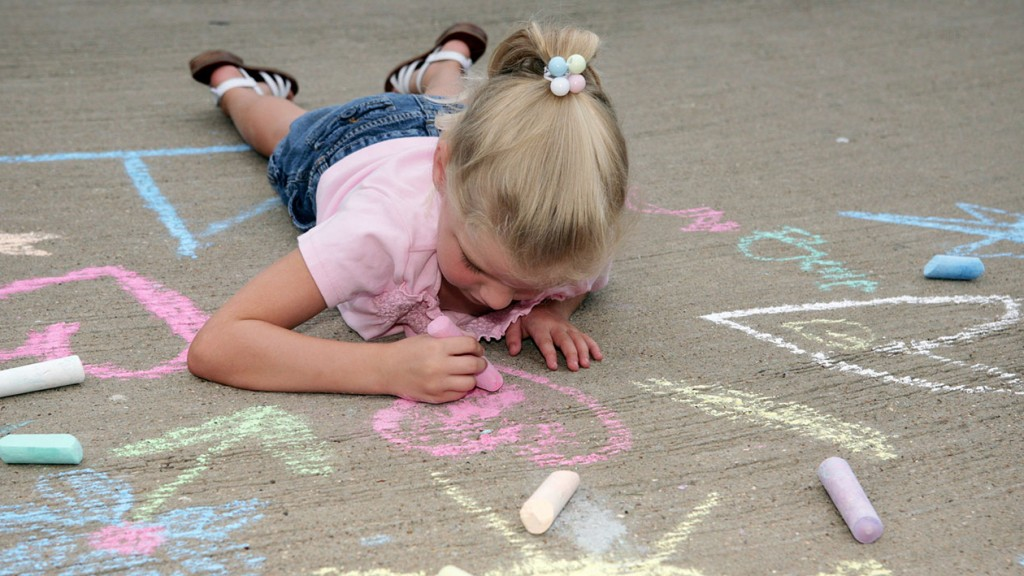 Little girl lying on pavement while drawing with chalk