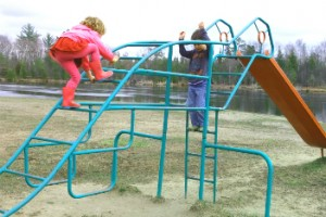 Young girl climbing on the monkey bars