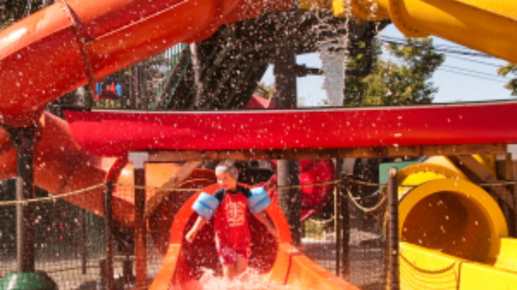 Photo of a kid at the end of a giant red waterslide