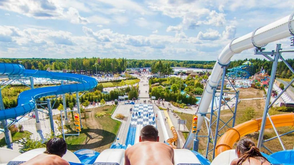 Photo of three kids about to slide down waterslide with view of park