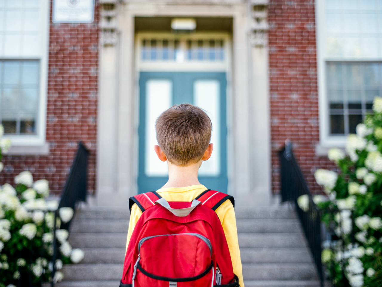 A little boy wearing a backpack standing in front of the school doors