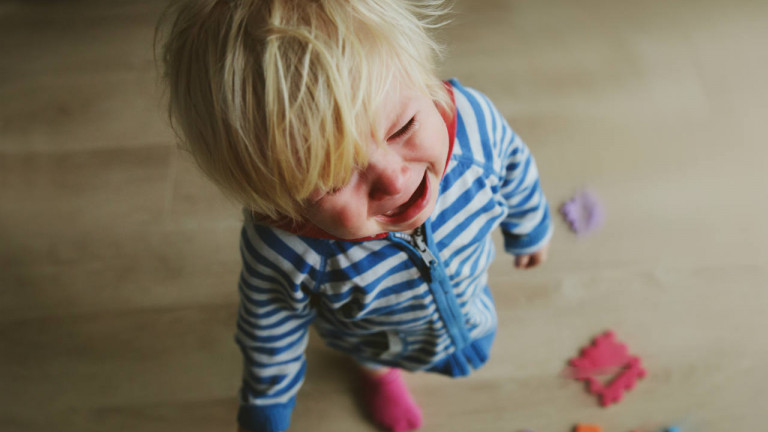 A little boy throwing a tantrum surrounded by colourful blocks