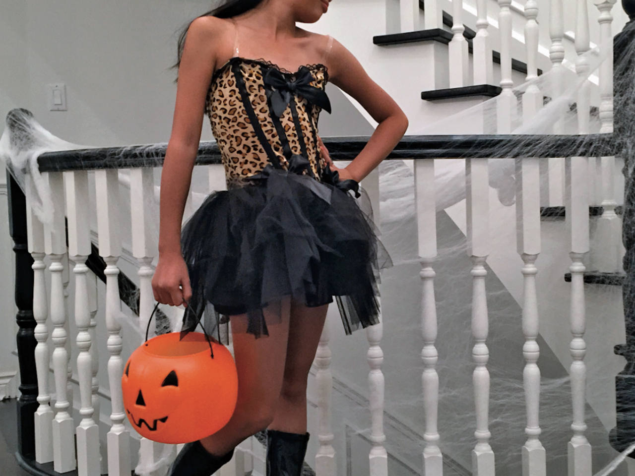 A girl dressed up in a leopard print dress holding a pumpkin treat bucket