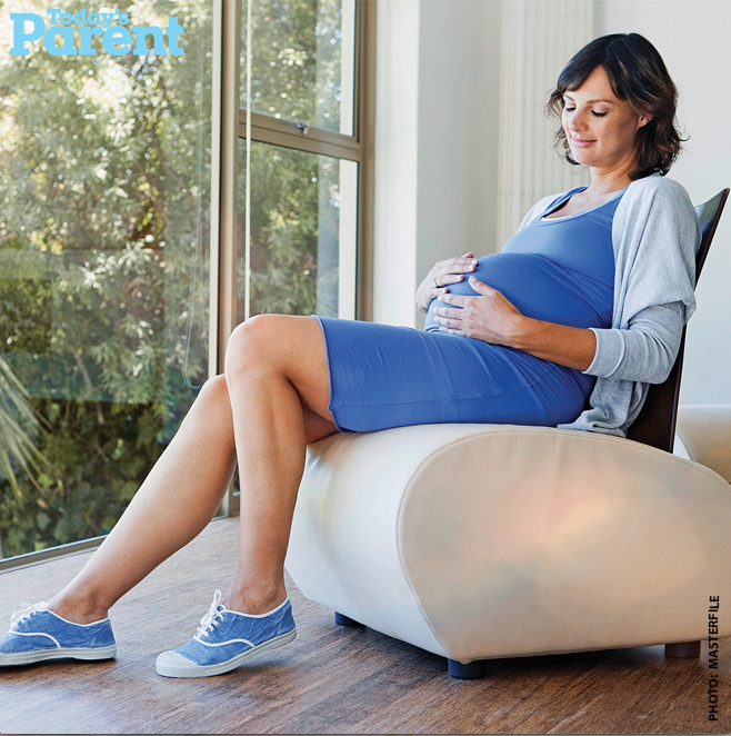 a pregnant woman sitting on a chair holding her belly