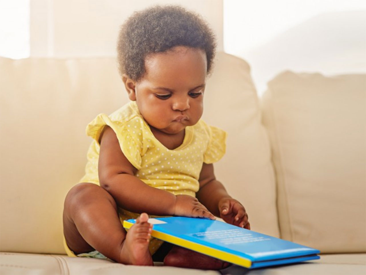 baby reading a book on the couch