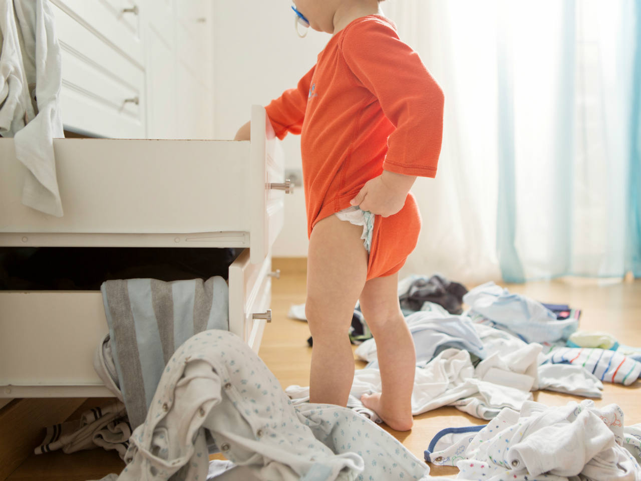 A toddler standing next a drawer and emptying out all the clothes