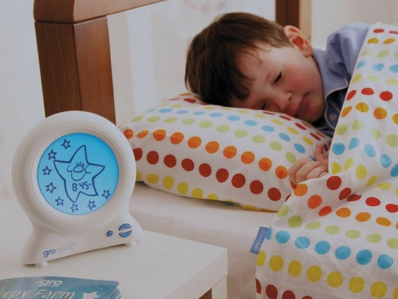 Child sleeping with their Gro Clock on the bedside table