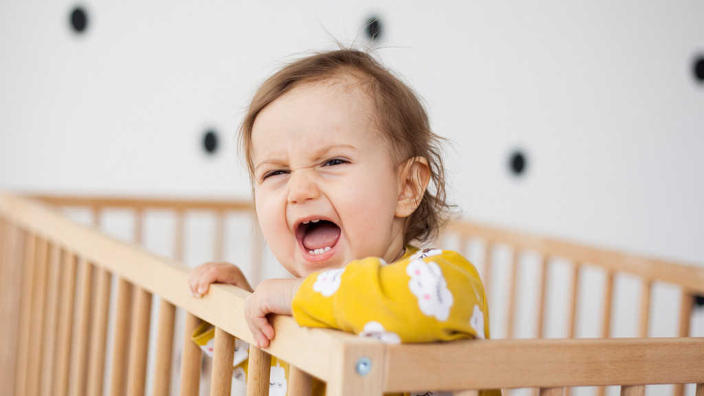 A little girl screaming in her crib