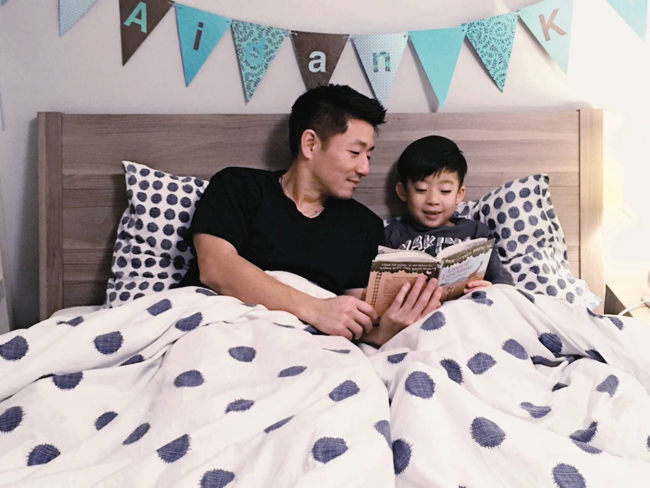 Father reading to his son in bed