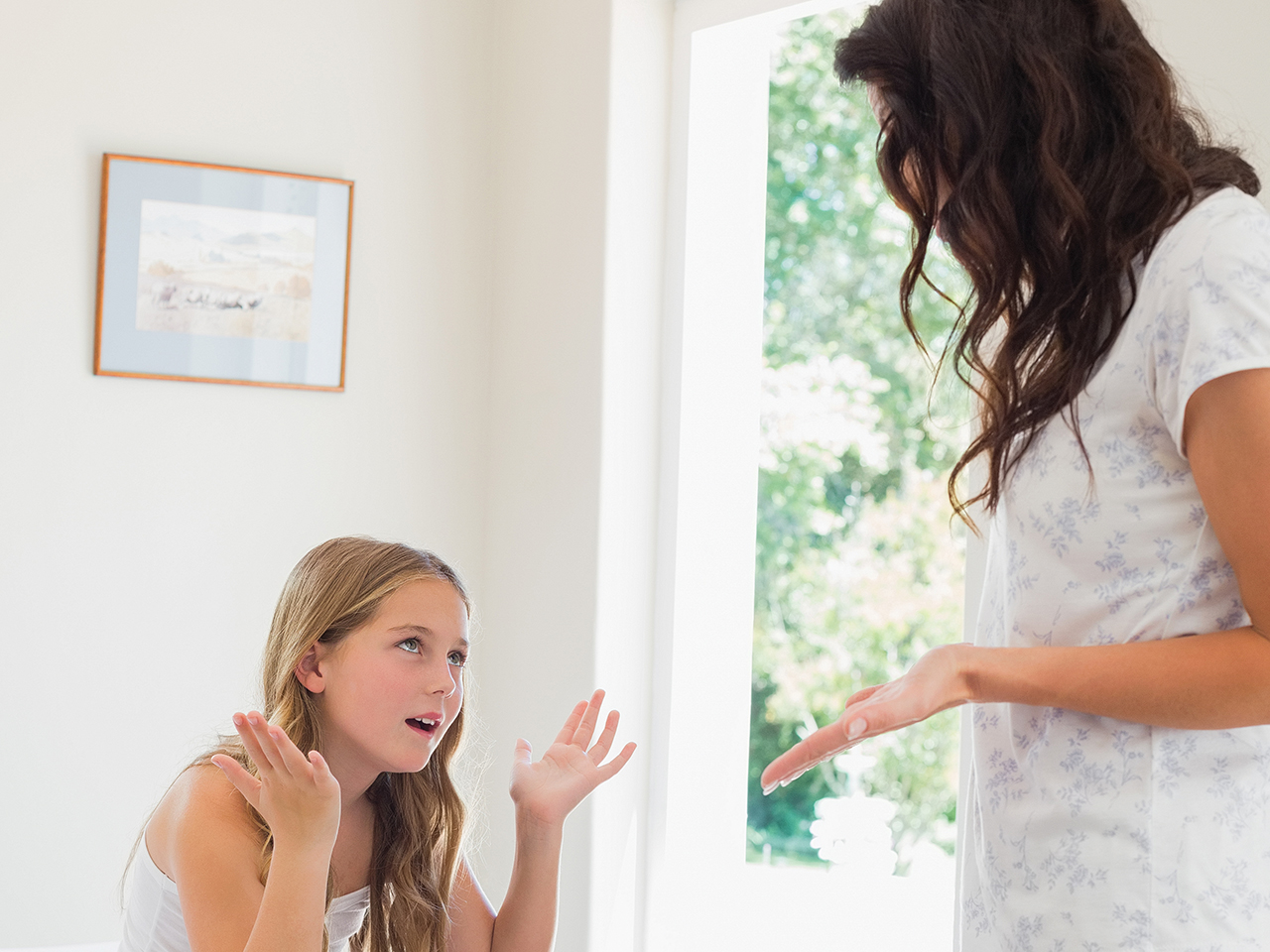 Mother and daughter arguing in bedroom at home about her tween moodiness