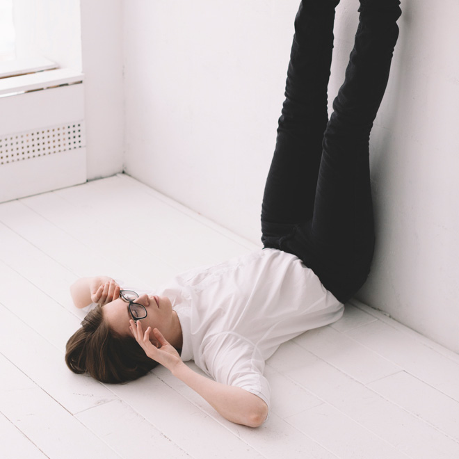 A woman lies on her back with her legs raised against a wall