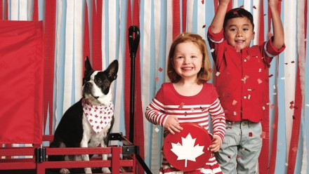 A little girl and boy decked out in red and white next to a dog in a wagon