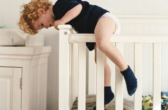 A little boy climbing out of his crib