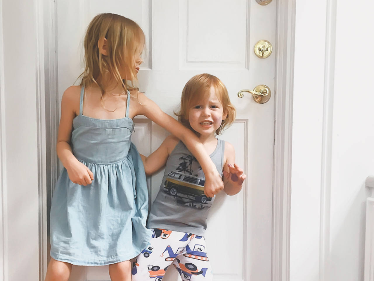 Two siblings pushing each other in front of the door
