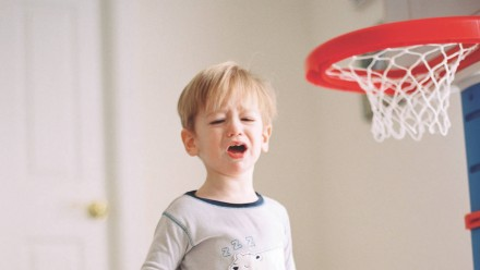 A little boy upset standing next to a basketball net