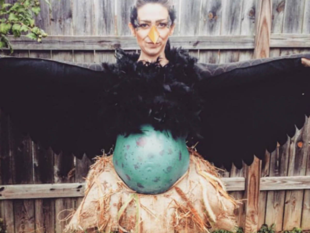 A pregnant woman dressed as a bird