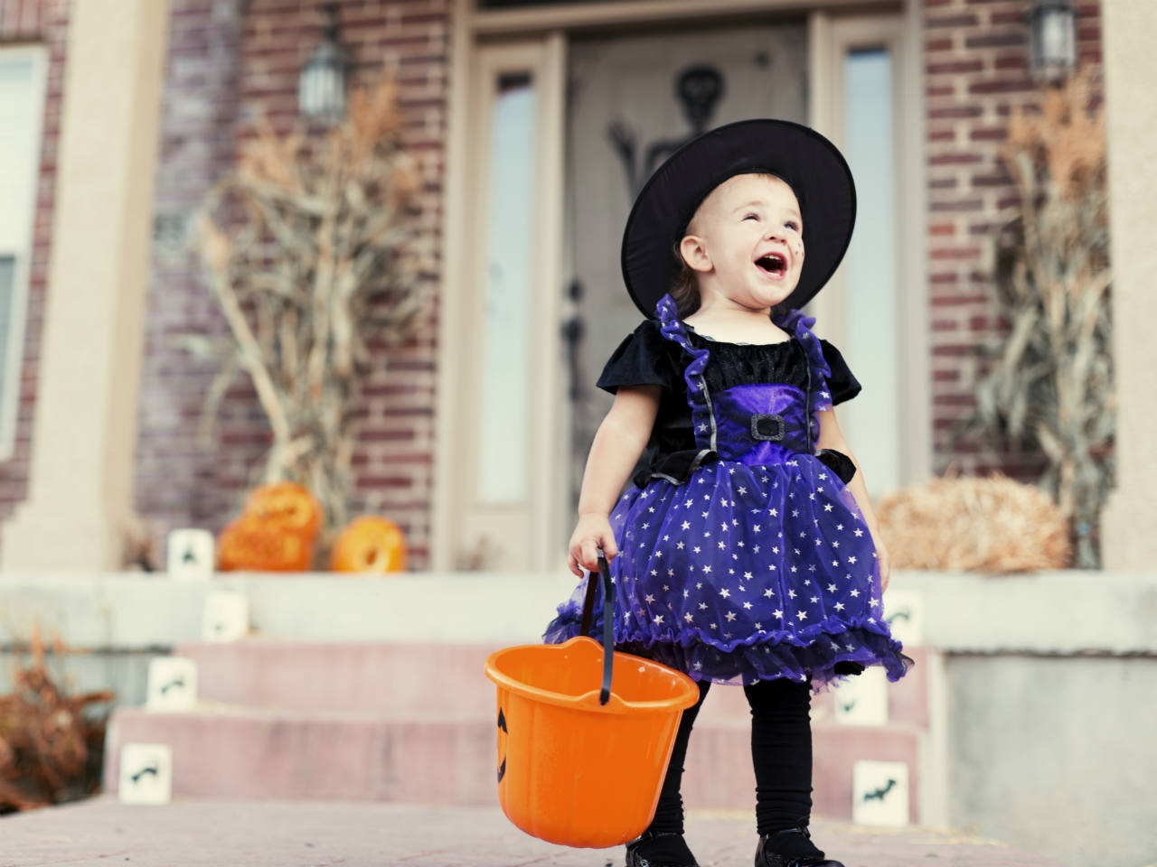 A little girl dressed as a witch standing on a doorstep on Halloween