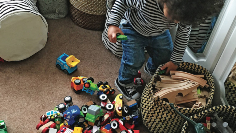 A little boy pulling trains out of a toy bin