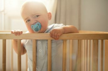 A baby standing up in a crib
