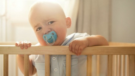 baby standing up in a crib with a soother looking grumpy