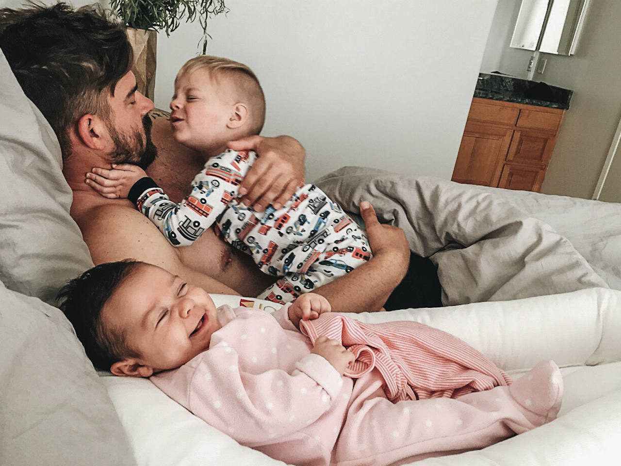 A dad in bed with his son on his chest and his baby next to him