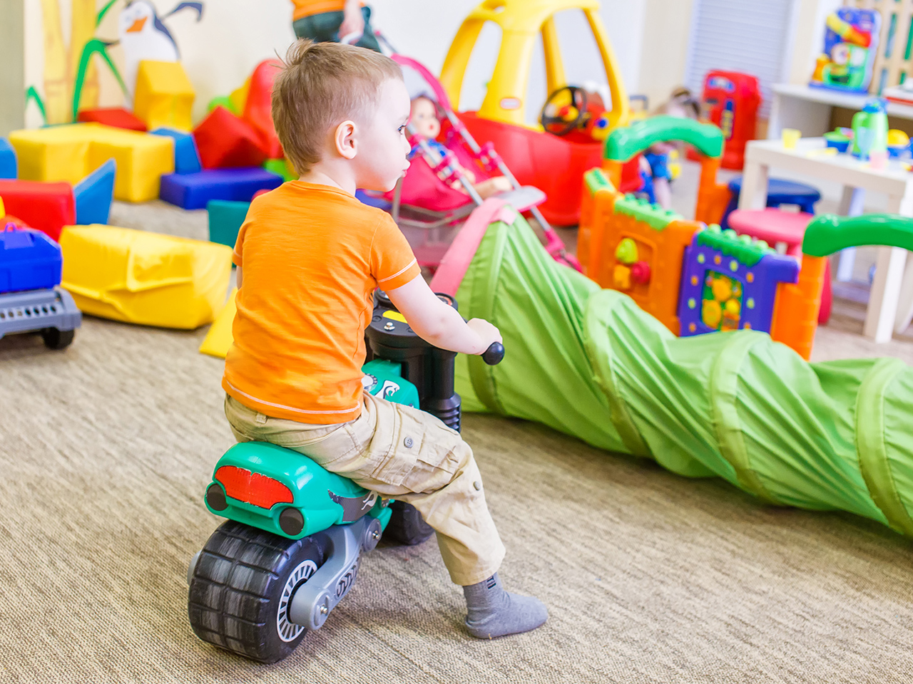 Little boy on motorbike faces playroom full of toys