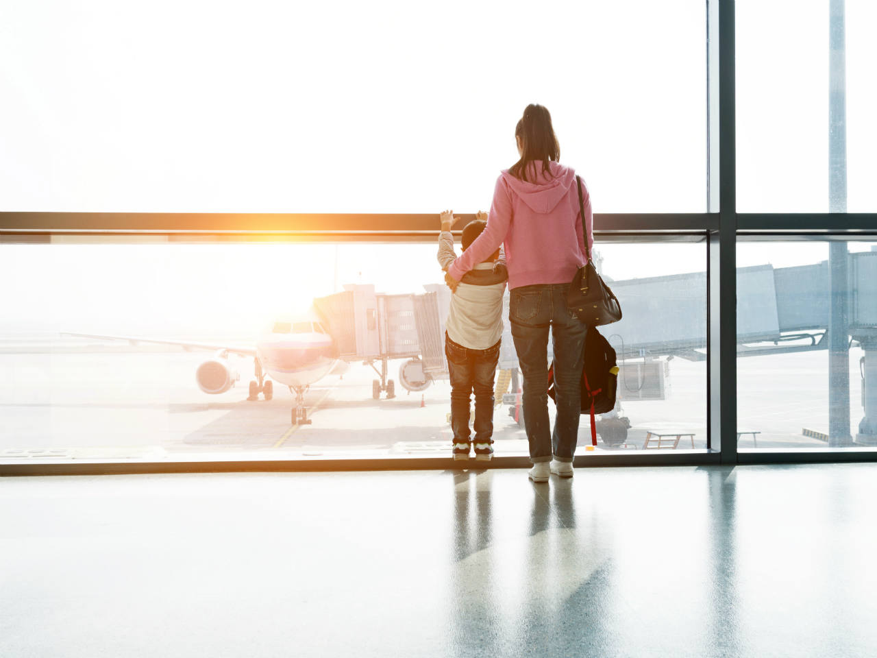 A woman and little boy looking out at an airplane