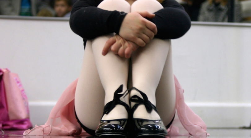 A little girl in ballet shoes and outfit sitting down and holding her knees