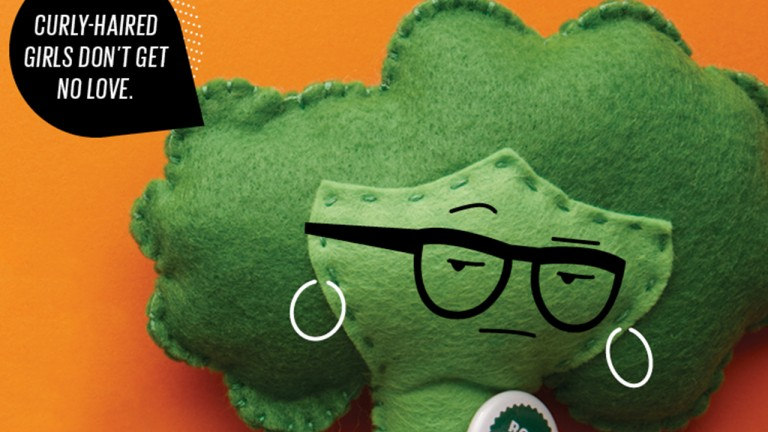 "A felt broccoli doll with glasses saying ""Curly-haired girls don't get no love"""