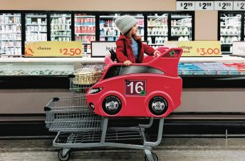 A little boy in a cart in a grocery store