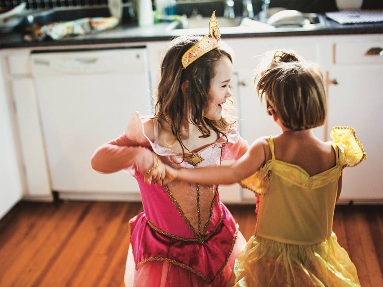 A little boy and girl dancing in princess dresses