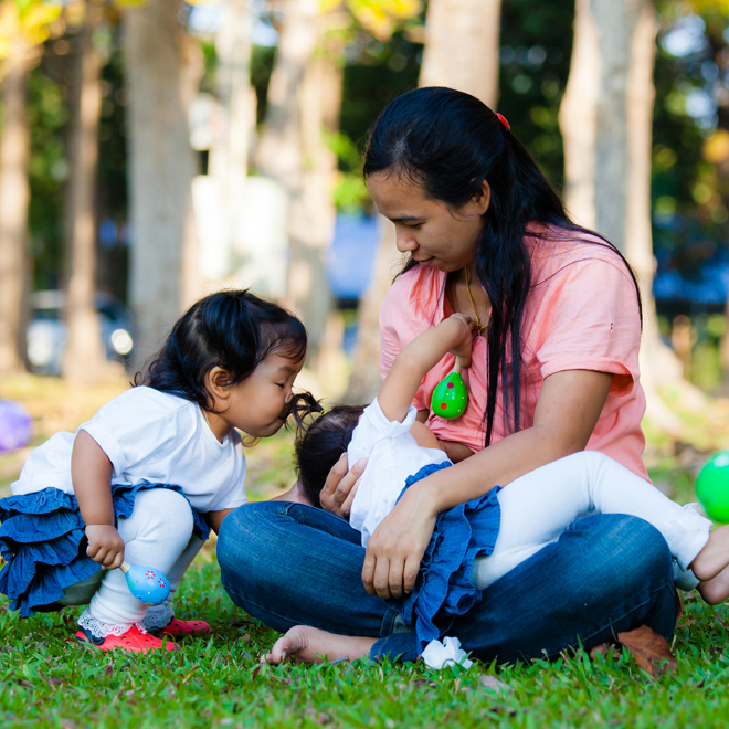 Woman breastfeeding her baby in a park