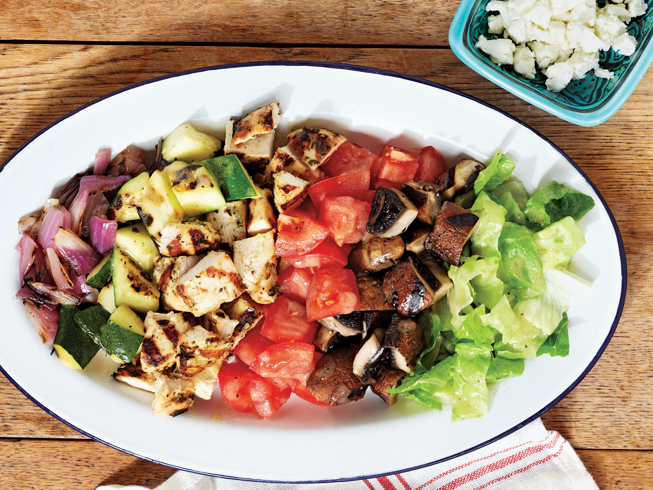 plate with grilled chicken, zucchini, red onion, mushrooms and lettuce and tomato
