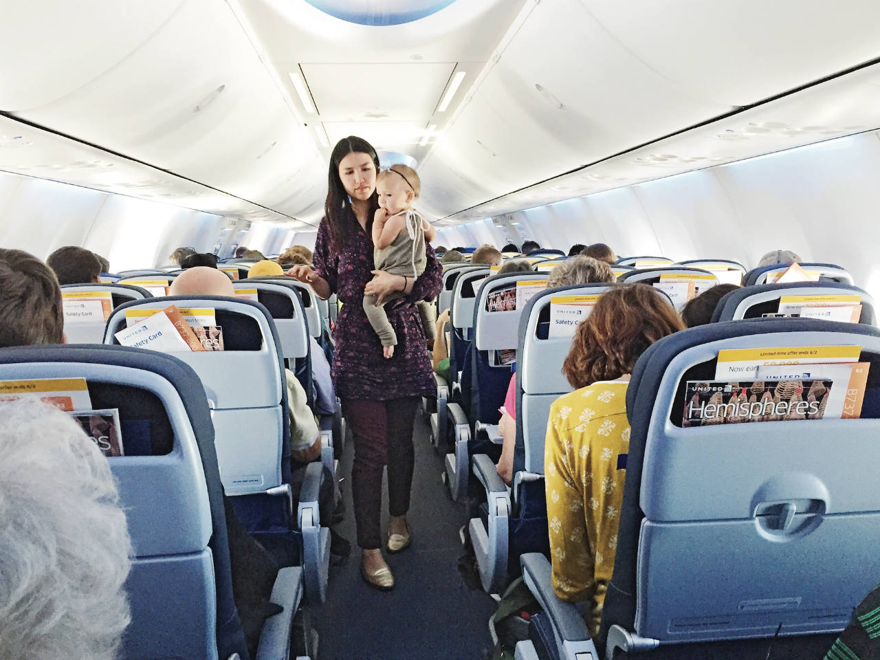 A woman with her toddler in her arms walking down a plane aisle