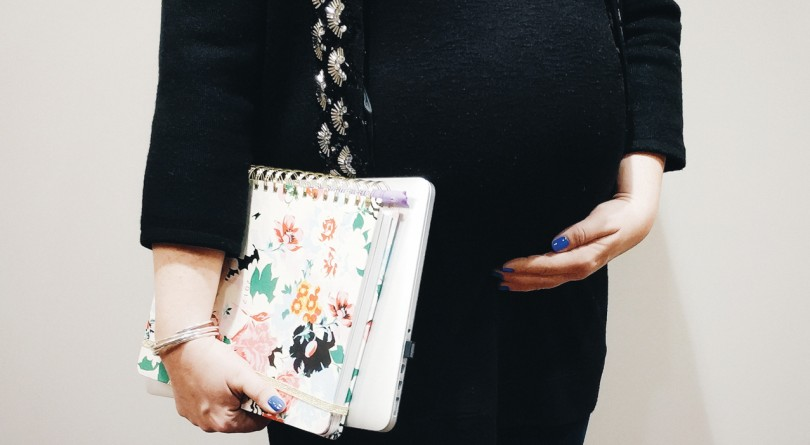 pregnant woman holds belly while holding notebooks